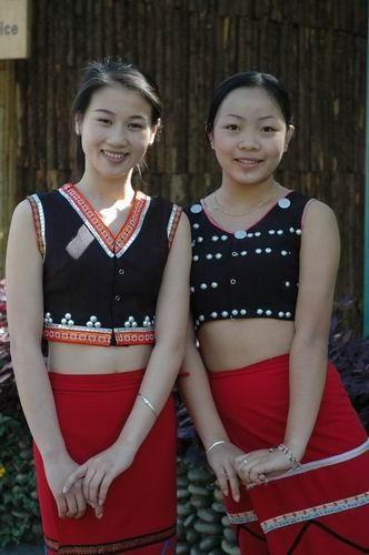 两个漂亮可爱的佤族小姑娘笑着过来打招呼